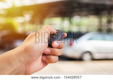 Men's hand presses on the remote control car alarm systems with sunlight