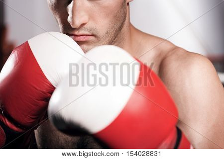 Self defense. Close-up of young boxer wearing red and white gloves and holding boxing position.