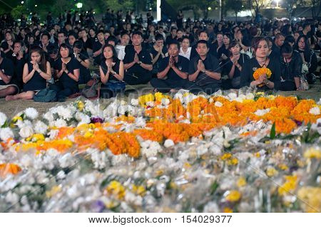 BANGKOK, THAILAND - OCTOBER 20, 2016 :Unidentified peoples put the palms of the hands together in salute, praying and put the flowers front of The King image at Sanam Luang park in Bangkok, Thailand.
