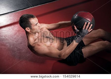 Top view of young brawny man lying on floor and doing some exercises with special fitness ball.