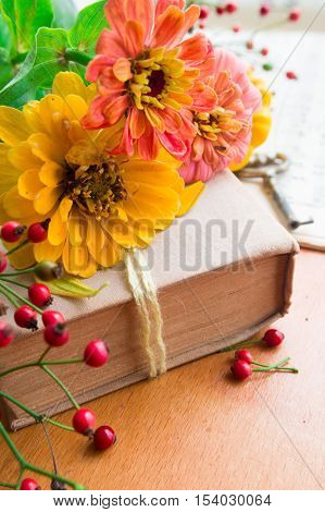 Old book with orange zinnia, key and autumn berries