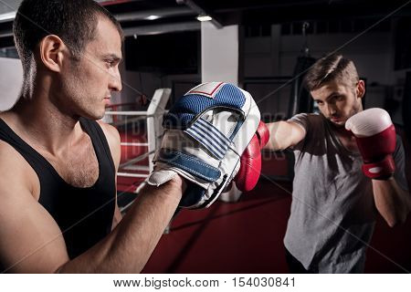 Concentrated on hook. Handsome young man holding boxing pad while his trainee working on hook.