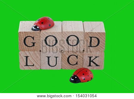 The words good luck and ladybugs on wood, isolated on green