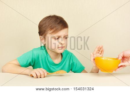 Little disaffected boy refuses to eat a cereal
