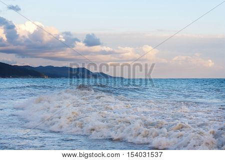 Raging surf waves on the beach in the evening of the mountainous coast