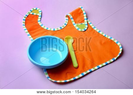 Bright baby tableware and bib on color background