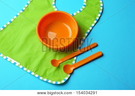 Bright baby tableware and bib on blue background