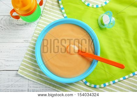 Plate with healthy baby food on table. Child feeding concept