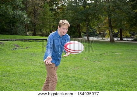 Blond Young Boy, In The Park Playing With A Rugby Ball