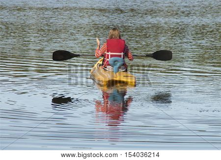 A woman heads out on her kayak to explore a small lake in a campground in Charleston South Carolina