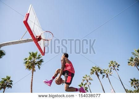 Basketball player making a dunk - Sportive man doing a spectacular dunk outdoors
