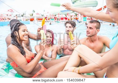 Multi-ethnic group of friends eating ice cream in a swimming pool - Young happy people having fun and enjoying summertime in a aquapark