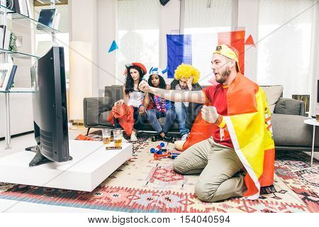 Spain supporter screaming and exulting for his team - Group of football fans watching match on tv at home