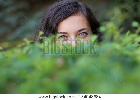 Timid glance from a woman behind the bushes.