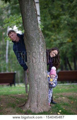 Happy family: Father, Mother and child - little girl walking in autumn park: mammy playing the airplane, telephoto shot