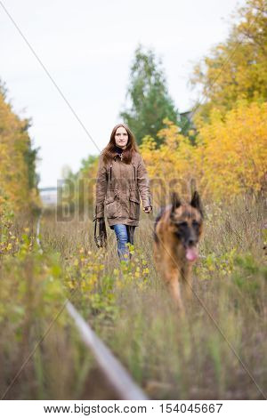 Attractive young woman walking with her dog German shepherd at autumn forest, near rail way - the girl is in focus, outdoor