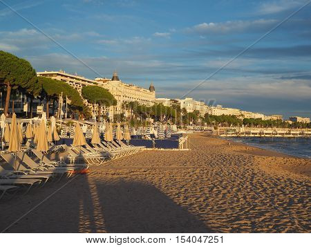 CANNES-SEPT. 13: The beach at dusk is seen in Cannes France with Carlton and Martinez hotel and cafes on famous Promenade de la Croisette on September 13 2015.
