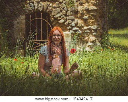 Portrait of pretty, young, cute woman in glasses sitting on green meadow with poppy flower, Pompeii, Italy, telephoto