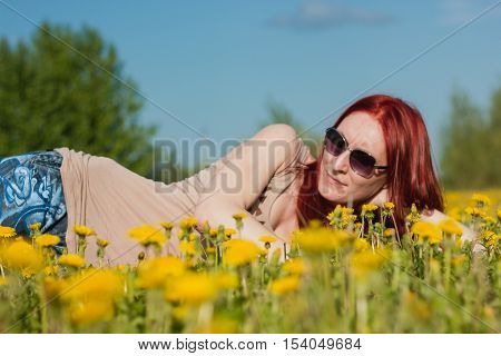 Young fashionable attractive sexy girl in glasses lying on a marguerite-meadow at sunny summer day, horizontal