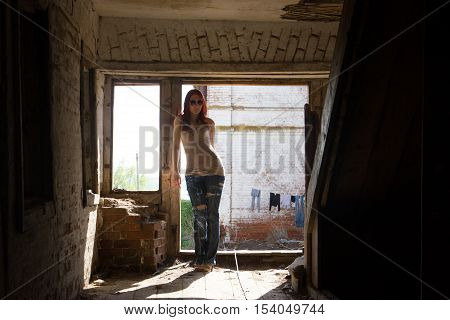 Young fashionable attractive sexy girl in glasses and jeans stands inside a destroyed building at sunny summer midday, horizontal