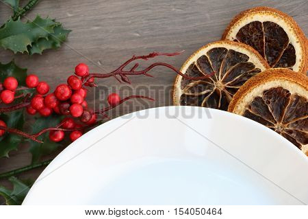 Traditional christmas (Xmas) festive decoration background with white plate on wooden background with dried orange and holly branch