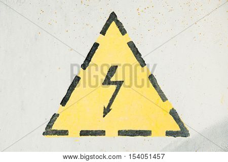 yellow high voltage sign with lightning on iron surface
