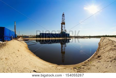 Drilling rig with reflection in the water. Siberia.