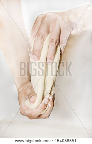 Image of the hands of a chef kneading dough on a floured counter top