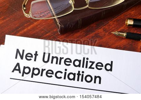 Papers with Net unrealized appreciation NUA on a table.