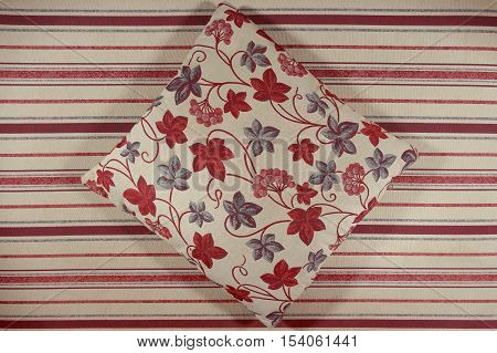 Decorative ornamental pillow. Fabric tapestry furniture. Floral and striped ornament.