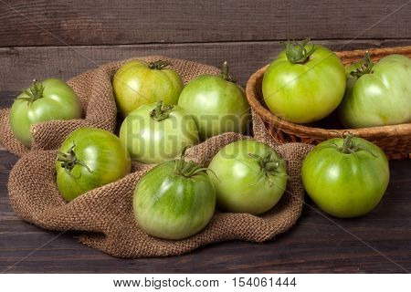 unripe green tomatoes on wooden table with sacking.