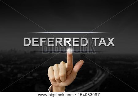 business hand clicking deferred tax button on black blurred background