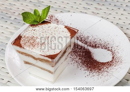 Delicious Dessert Tiramisu In A Square Glass On A White Plate