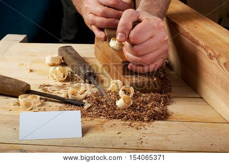 Blank business card on wooden table for carpenter tools with sawdust.Copy space. Top view.