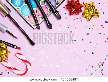 Makeup for festive party. Red lipstick, liquid eyeliner, mascara, bright color glitter eyeshadow, brushes and applicator with candy cane, gift wrap bow and confetti on pink background. Copy space