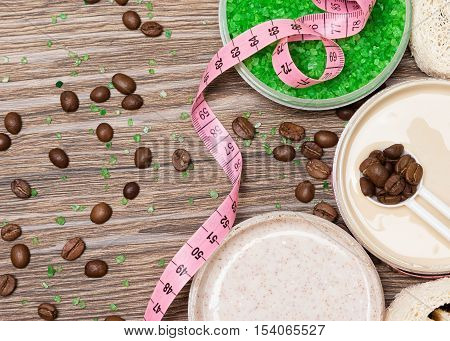 Anti-cellulite cosmetic products with caffeine. Open jars filled with cellulite cream containing coffee essential oil, sea salt, natural body scrub, coffee beans and body measuring tape. Copy space