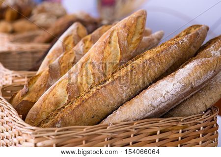 Fresh baguettes bread in a basket. Many baguettes