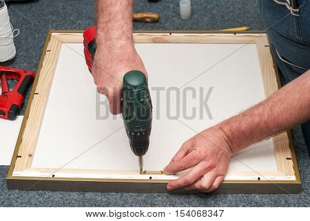 Craftsman working on frame in frame shop. Professional framer hand holding frame angle. Top view. Copy space.