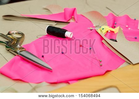 Sewing textile or cloth. Work table of a tailor. Textile tools. Scissors reel of thread,  measuring tapes and natural fabric. Copy space.