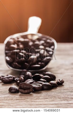 Close up coffee beans and big stainless steel scoop on wooden table with sun light
