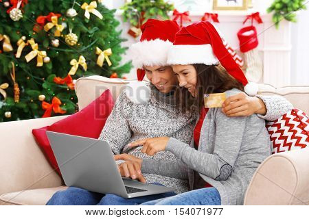 Young couple shopping online with credit card at home for Christmas