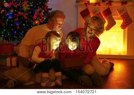 Elderly couple with their granddaughters opening Christmas present near fireplace