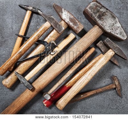 Tool background. Old vintage hammer and pincers tools collection on wooden workbench. Copy space. Top view flat lay