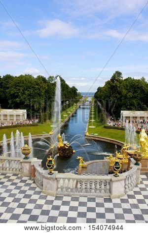SAINT-PETERSBURG, RUSSIA - AUGUST 16, 2012: View from Grand Petergof Palace to Lower park with Grand Cascade Fountains, golden statues, and water canal.