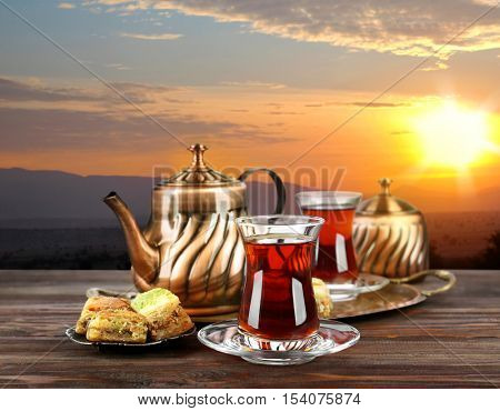 Composition for Turkish tea ceremony on wooden table against landscape background. Culture heritage concept.