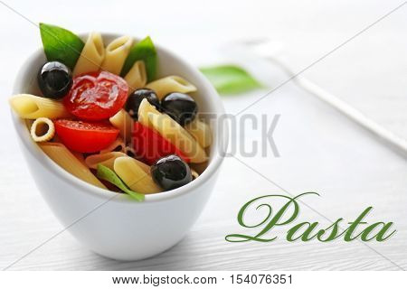 Bowl of delicious pasta, closeup. Italian food concept. Word PASTA on background.