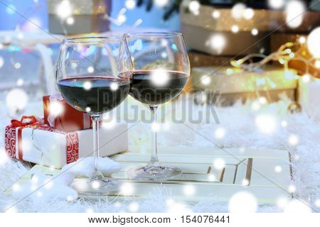 Glasses of red wine on blurred Christmas interior background. Christmas celebration concept.