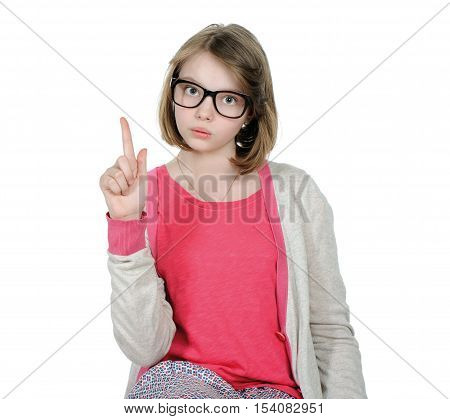 Portrait Of A Cute Young Girl With A Raised Index Finger.