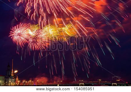Fireworks over Neva river view to Spit of Vasilyevsky Island at victory day, 9th may. Fireworks have long sparkles beside cloud at night. Saint Petersburg, Russian.