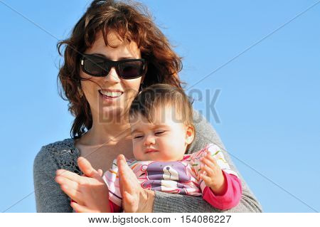 Mother shows her baby 9 month old daughter how to clap her hands with a blue sky in the background